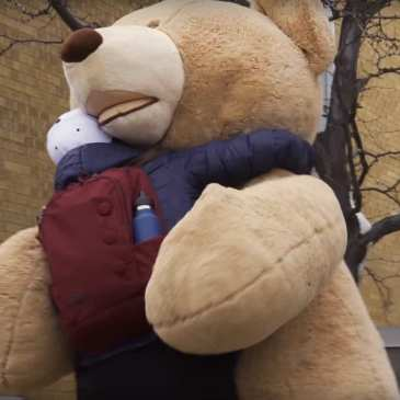 A giant teddy bear celebrates Valentine's Day by giving hugs and flowers (video)